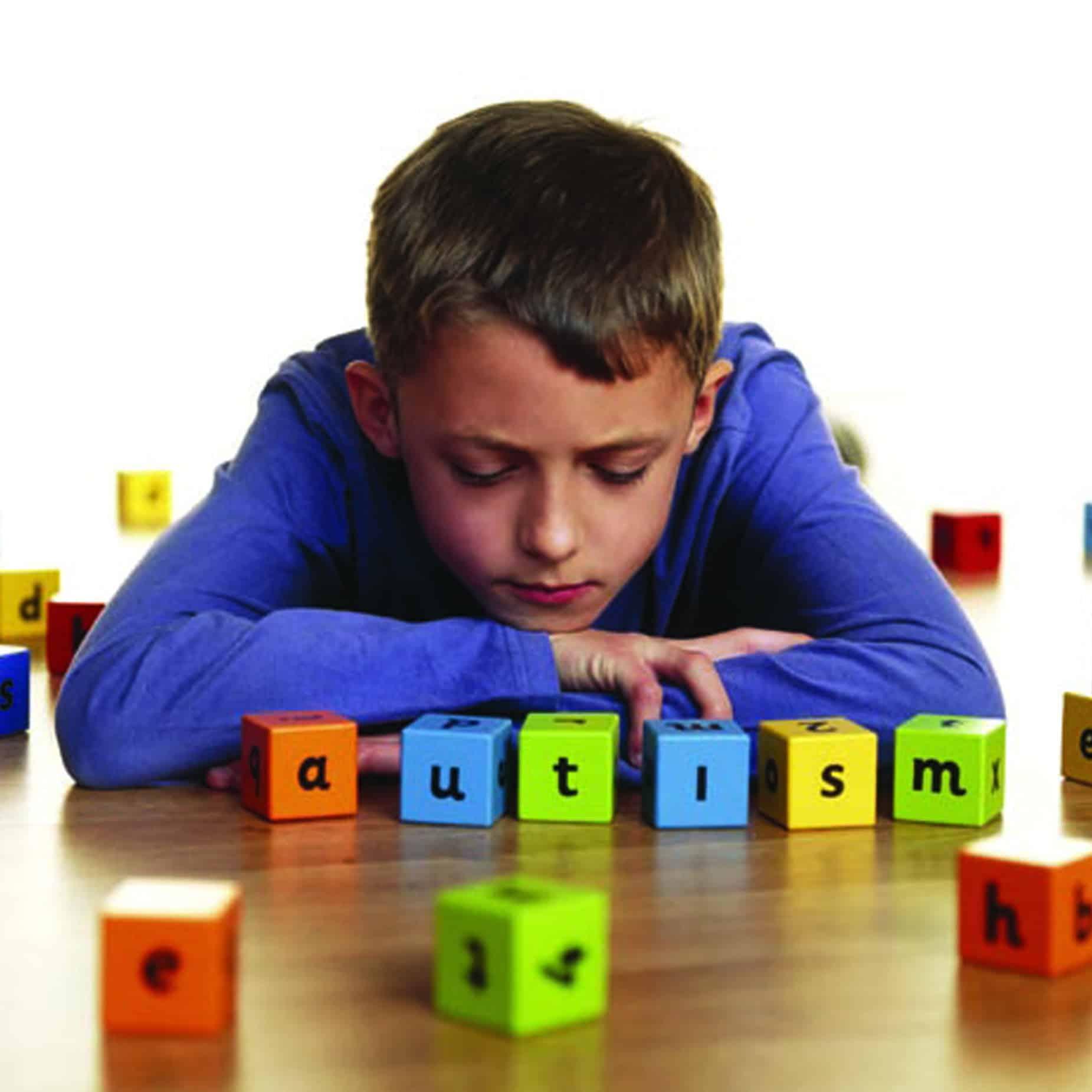 A boy staring at his toy blocks - NAET Dubai