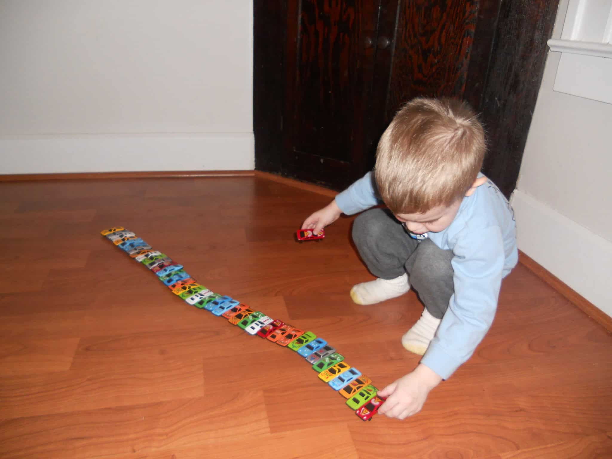 A boy playing his toys in a line order - NAET Dubai